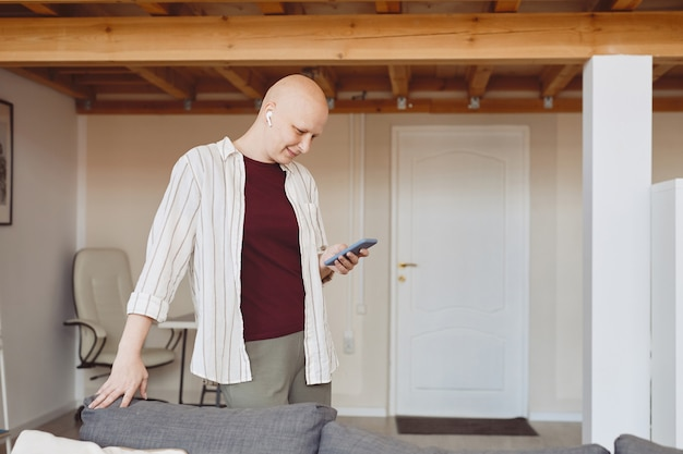 Side view portrait of smiling bald woman using smartphone with wireless earphones while enjoying music at home in modern interior, alopecia and cancer awareness, copy space