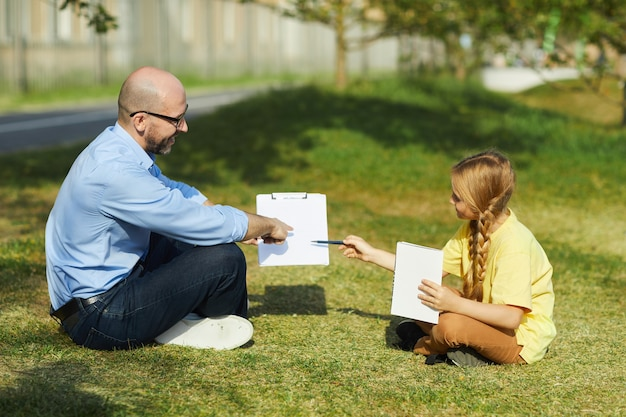 Side view portrait of smiling mature man sitting on green grass and pointing at clipboard while explaining lesson to little girl during outdoor class, copy space