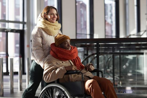 Вид сбоку портрет улыбается молодой женщины, помогающей афроамериканскому мужчине в инвалидной коляске на станции метро, копией пространства