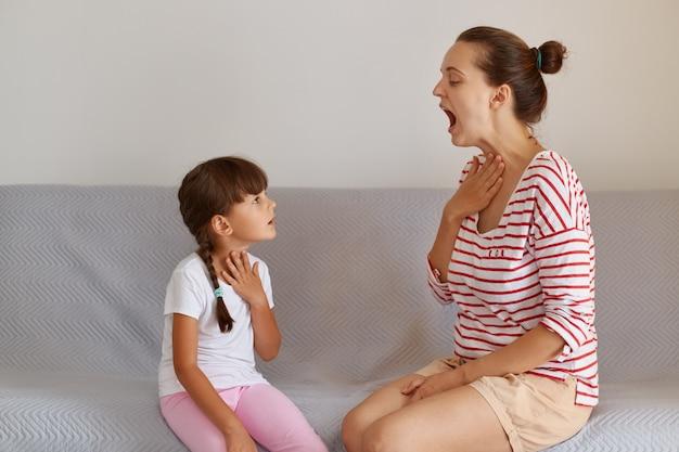 Ritratto di vista laterale del logopedista che dimostra per il bambino come pronunciare i suoni giusti, fisioterapista professionista che lavora sui difetti del linguaggio con una bambina piccola al chiuso.