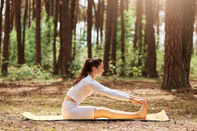 Side view portrait of sportswear sitting in sit-up position in open air, yoga training in forest, workout on nature, relaxing and meditation, healthy lifestyle.