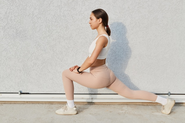 Side view portrait of sporty woman with dark hair and ponytail wearing white top and beige leggins, stretching legs before or after training outdoor, isolated over gray background.