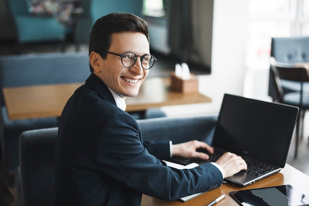 Side view portrait of a stylish adult caucasian manager wearing suit and glasses  smiling over his shoulder while working at laptop in cafe.
