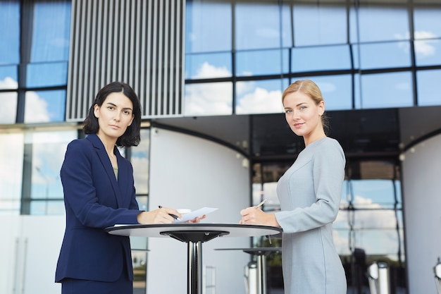 Side view portrait of two businesswomen smiling at camera while standing by cafe table in airport or office building,