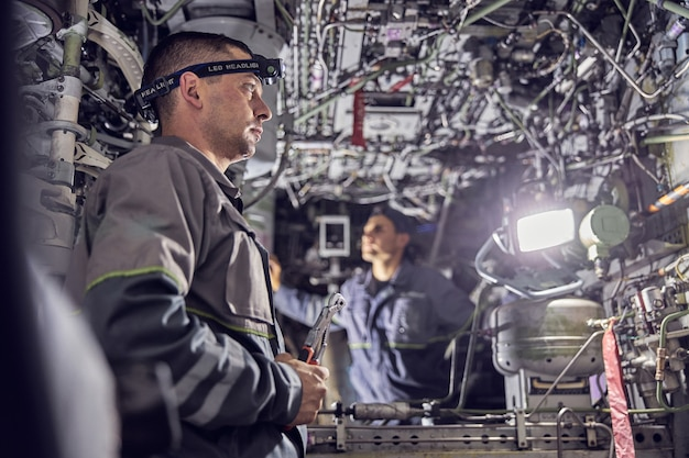 Side view portrait of two confident engineer working with electrical system of passenger aircraft