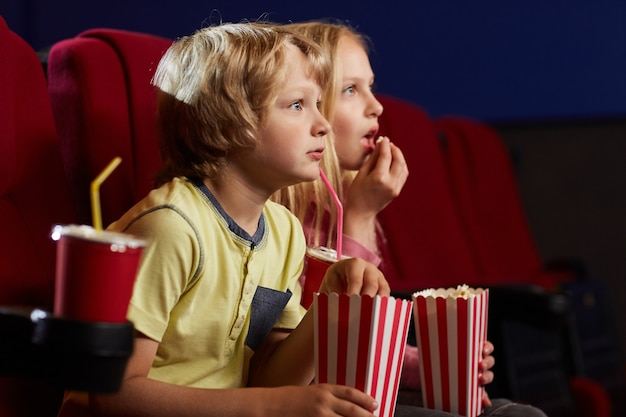 Side view portrait of two kids with open mouths watching movie in cinema theater and eating popcorn, copy space