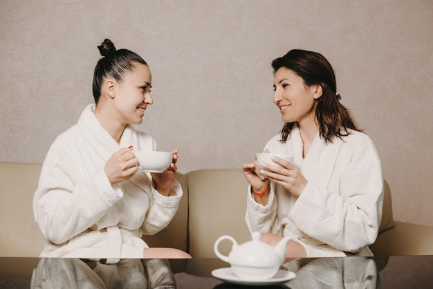 Side view portrait of two lovely woman talking with a cup of tea in their hands after spa procedures dressed in bathrobe in a wellness spa center.