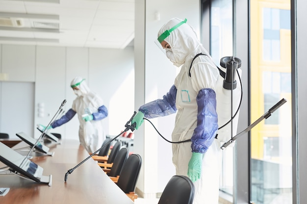 Side view portrait of two workers wearing hazmat suits disinfecting conference room in office,