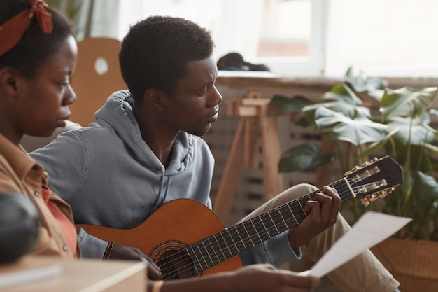 Side view portrait of two young african-american musicians playing guitar and writing music together while sitting on floor in recording studio, copy space