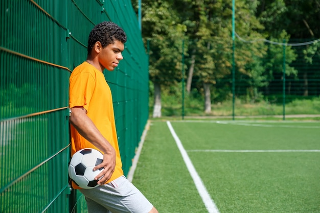 Side view portrait of young african-american man holding soccer ball while standing with back against fence in sports court outdoors, copy space