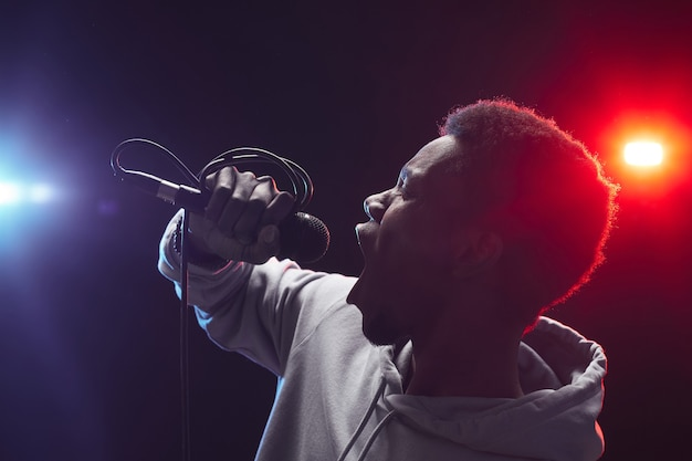 Side view portrait of young african-american man singing to microphone emotionally while standing on stage in lights