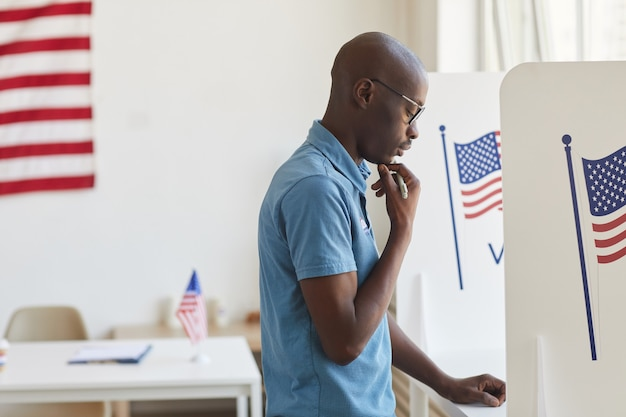 Side view portrait of young african-american man standing in voting booth and thinking, copy space