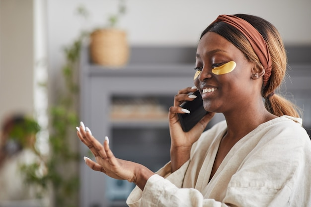 Side view portrait of young african-american woman enjoying beauty routine at home and speaking by smartphone while looking at nails, copy space