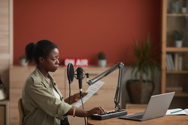 Side view portrait of young african-american woman playing keyboard while composing music in home recording studio, copy space