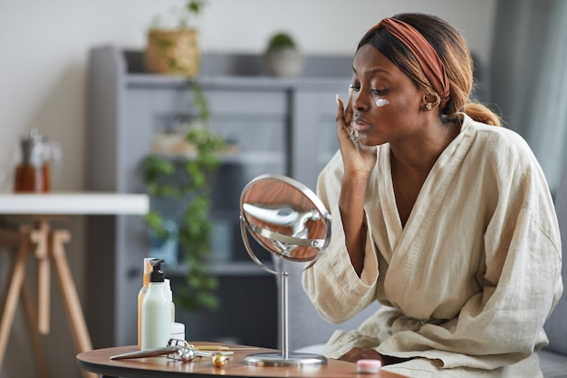 Side view portrait of young african-american woman using face cream or moisturizer, skincare and beauty routine concept, copy space