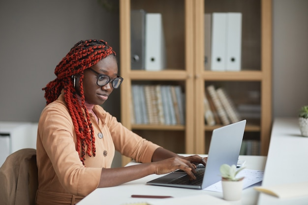 Side view portrait of young african-american woman using laptop while studying or working from home at workplace, copy space