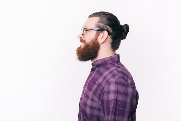 Side view portrait of young bearded man wearing eyeglasses