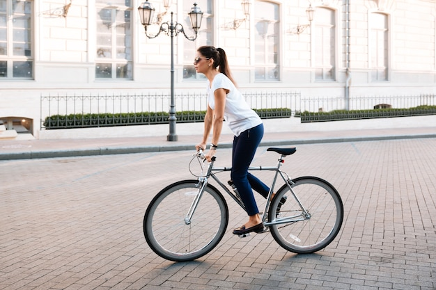 Side view portrait of a young beautiful woman riding on bicycle in city street