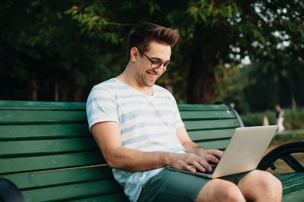 Side view portrait of a young confident freelancer working outdoor in the park on his laptop smiling.