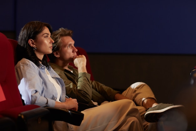 Side view portrait of young couple in cinema watching movie while sitting on red velvet chairs in dark room and looking up with serious face expressions, copy space
