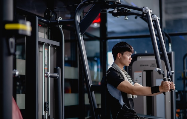 Side view, portrait young handsome man in sportswear sitting for doing machine chest press exercise in modern gym, looking forward,