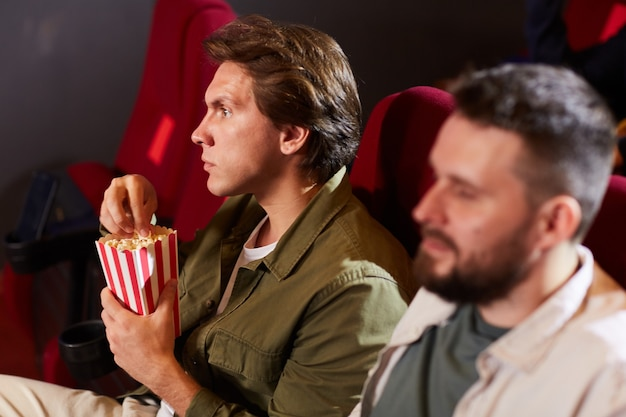 Side view portrait of young man eating popcorn while watching movie in cinema theater with other people in foreground, copy space