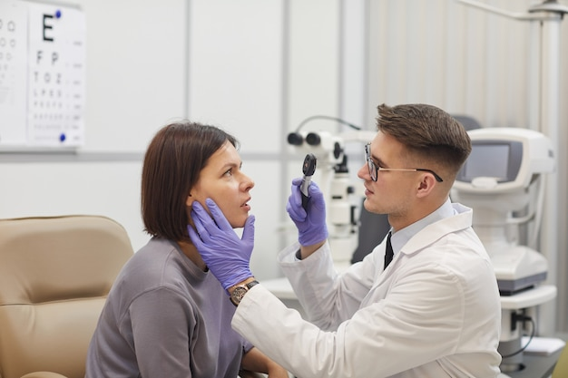 Side view portrait of young ophthalmologist checking eyesight of female patient