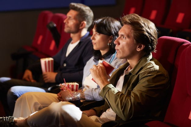 Side view portrait of young people watching movie in cinema while sitting in row on red velvet chairs, focus on man drinking soda through straw with tense face expression, copy space