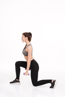 Side view portrait of a young pretty sportswoman doing squats with dumbbells isolated