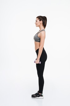 Side view portrait of a young sports woman standing with dumbbells isolated on a white backgorund