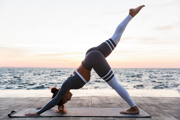 Side view portrait of a young woman doing yoga exercises