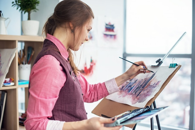 Side view portrait of a young woman painter drawing cityscape with watercolor palette on white paper using easel.