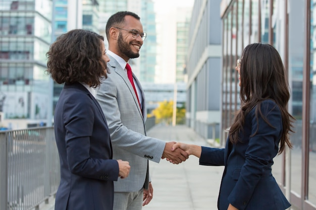 Side view of positive business people handshake