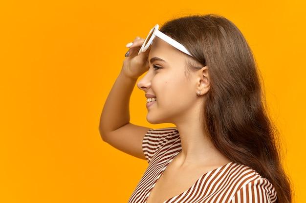 Vista laterale della giovane signora gioiosa positiva in vestito da estate a strisce che toglie gli occhiali da sole alla moda