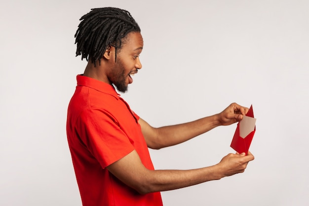 Side view of positive man opening letter in red envelope, holding greeting card and feels happy.
