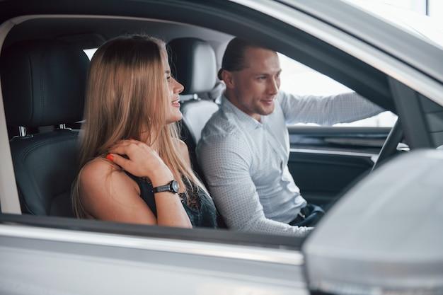 Вид сбоку. позитивный менеджер, показывающий покупательнице особенности нового автомобиля