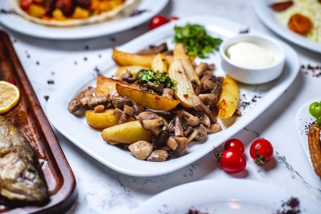 Вид сбоку картофель с жареными грибами картофель с шампиньонами, зеленью, сметаной и помидорами на столе