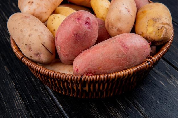 Vista laterale della merce nel carrello delle patate sulla tavola di legno
