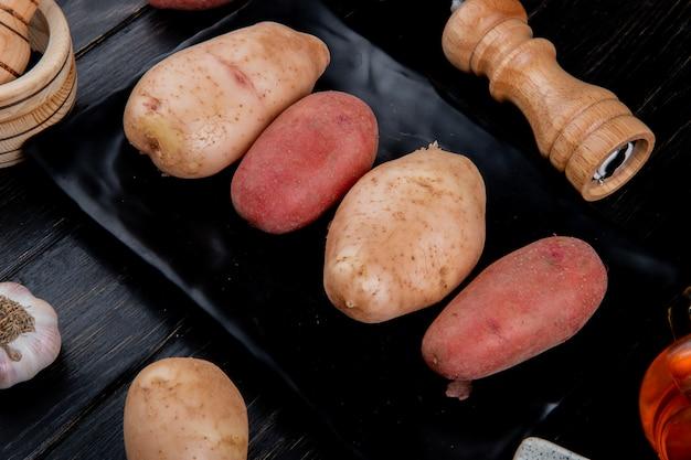 Vista laterale delle patate in zolla con sale e aglio sulla tabella di legno