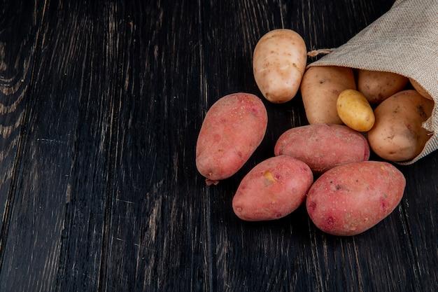 Vista laterale delle patate che si rovesciano dal sacco sulla tavola di legno con lo spazio della copia