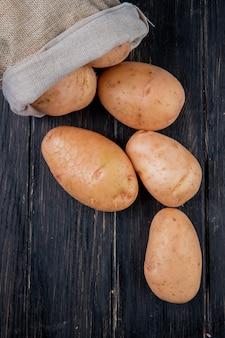 Vista laterale delle patate che si rovesciano dal sacco sulla tavola di legno