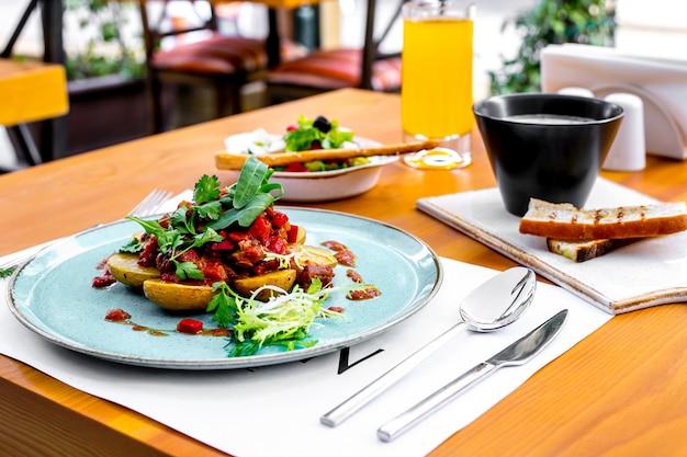 Patate vista laterale con carne in salsa di pomodoro con rucola e insalata greca e zuppa sul tavolo