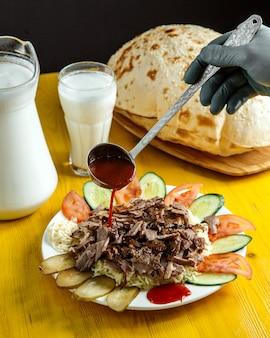 La vista laterale di salsa di versamento su doner sul piatto è servito con i cetrioli e i pomodori freschi dei sottaceti