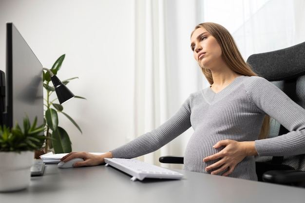 Side view of pregnant businesswoman at her desk holding her belly