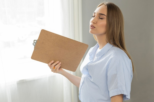 Side view of pregnant businesswoman holding clipboard while in pain