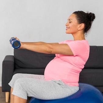 Vista laterale della donna incinta che esercitano a casa sul pavimento con palla e pesi