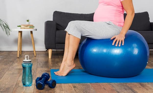 Vista laterale della donna incinta che si esercita a casa sul pavimento con la palla
