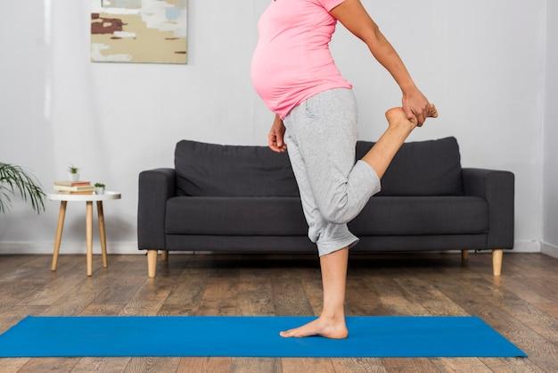 Vista laterale della donna incinta che si esercita a casa su materassini