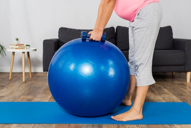 Side view of pregnant woman exercising at home with weights and ball
