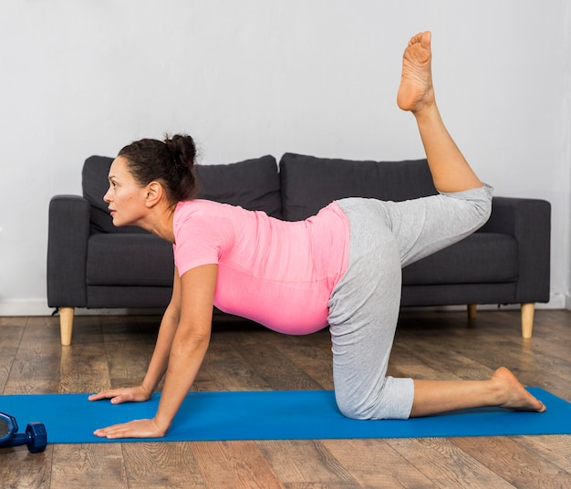 Side view of pregnant woman exercising on mat at home